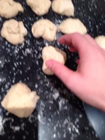 Rollo de cada pieza en una bola apretada y preparar 2 bandejas para hornear espolvoreando con harina o poner papel de horno sobre ellos