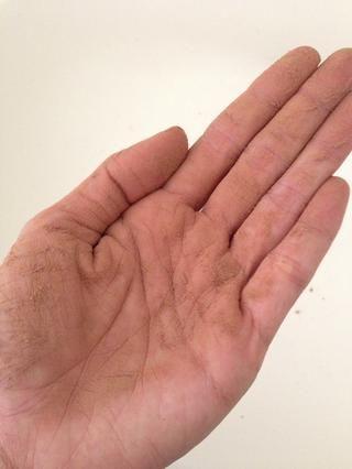 Frunce su mano alrededor de lo que el polvo se recubre de manera uniforme en su mano.