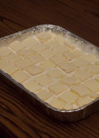 Cúbrase la mezcla de torta con las rebanadas de mantequilla.
