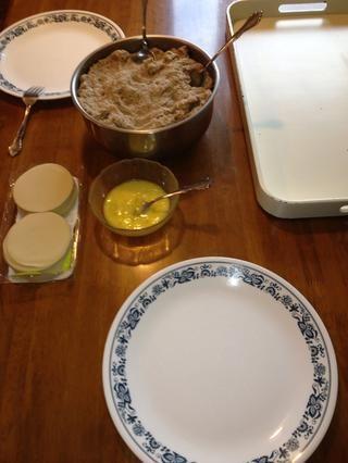 Prepare a su estación de trabajo: pieles de wonton, 1 huevo batido, un plato por persona trabajadora, una bandeja grande enharinada o un plato para sus wontons completados, una toalla de papel (no se muestra) por persona de trabajo, y la mezcla de carne de vacuno.
