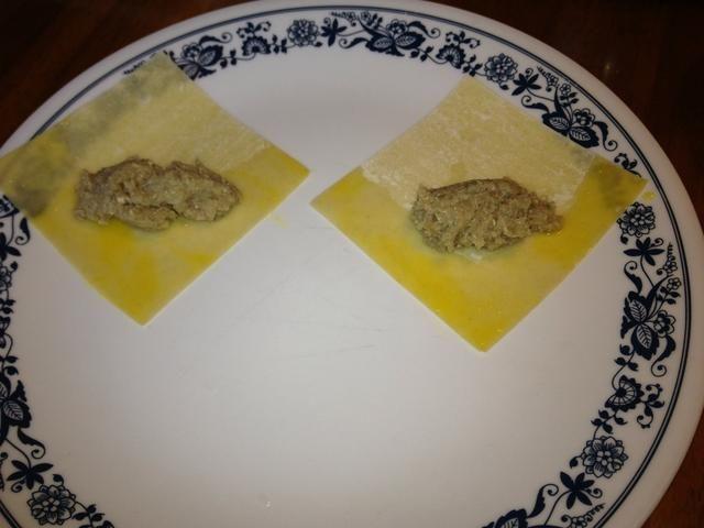 Sumerja 2 bordes de la piel wonton plaza en el huevo. Asegúrese de que sólo una de las superficies se azuzaba. Es decir, hay shouldn't be egg on the surface sitting directly on the plate. Add a small amount of beef mix.