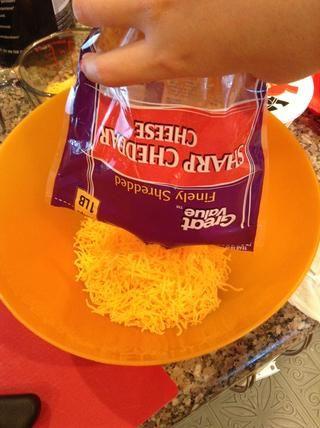 En un tazón grande, agregue 3,75 tazas de queso cheddar.