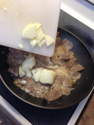 Empuje de res a la sartén bordes y añadir la cebolla en rodajas.