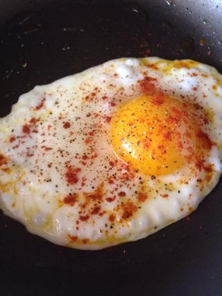 Freír el huevo Sunny Side Up en aceite de oliva y sazone con pimienta negro y pimentón (I don't salt the egg because we salted the cucumbers, salmon is salty too). Turn the egg over and make over easy egg..