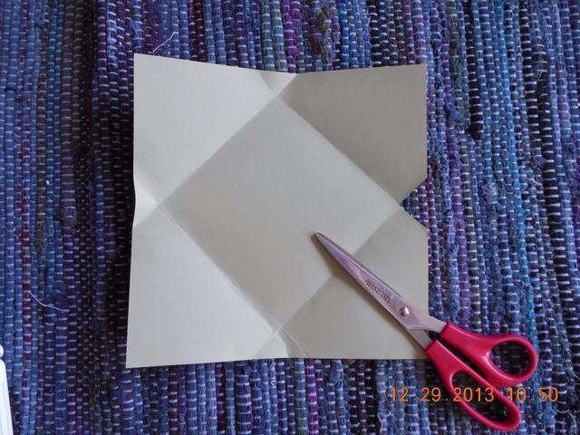 Usted tendrá pequeños triángulos en el borde medio de su papel arrugado. Recorta los pequeños triángulos como en la foto.