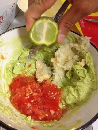 Revuelva el tomate, la cebolla, el ajo y el jugo de limón en el aguacate.