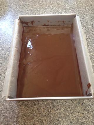Ponga un molde para hornear en el congelador en una superficie plana (por lo que el chocolate doesn't run to one side and cool unevenly) for 20 minutes.