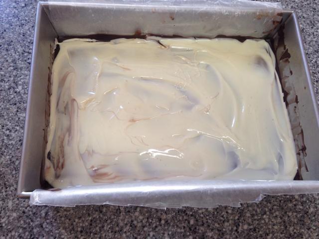Spread derretido el chocolate blanco sobre el chocolate negro congelado, trabajando rápidamente el chocolate congelado empezará a enfriar el chocolate blanco.