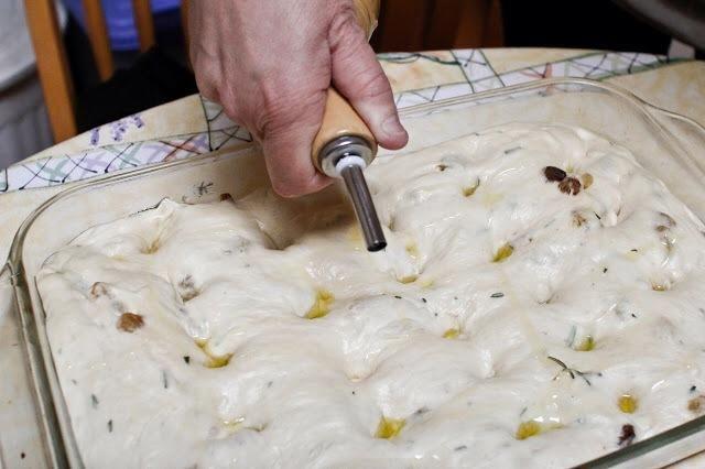 Rocíe el aceite de Oilve sobre la masa en las pequeñas hendiduras.