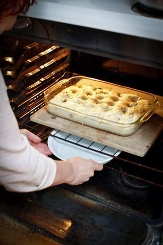 Justo antes de la cocción, ponga un molde para pay u otro recipiente con agua por debajo de la piedra de la pizza para la humedad adecuada. Deslice la focaccia en el horno.