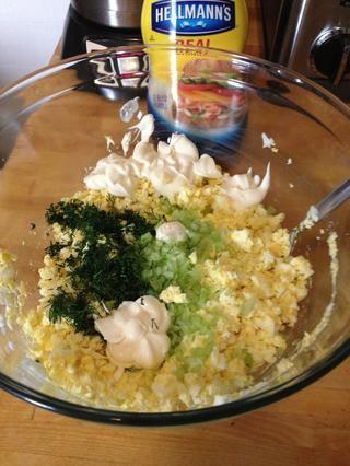 Añadir el eneldo fresco, mayonesa y apio a la mezcla de yema de huevo y mezclar con un tenedor.