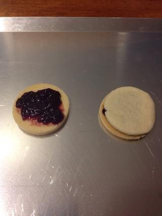 Una vez que las cookies se han enfriado colocar un poco de mermelada de frambuesa roja en la cookie y cubra con otra galleta para hacer un sándwich. Continúe hasta que todas las cookies se han agotado.