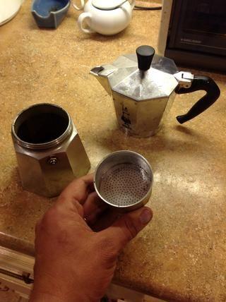 He aquí un vistazo a la cafetera estufa. La canasta que tengo en mi mano es donde va el café. Encaja en el pozo de agua que se ve a la izquierda. El café acabado entra en el bote hasta la parte superior.