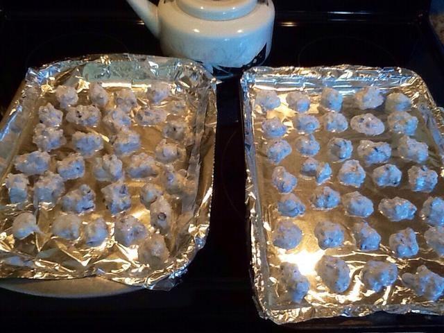 Caída de las cookies por cucharadita en papel de aluminio cubierto bandejas para hornear sin engrasar.