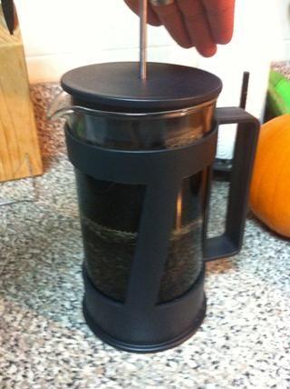 Siguiente presione lentamente el émbolo hacia abajo para separar los motivos y café.