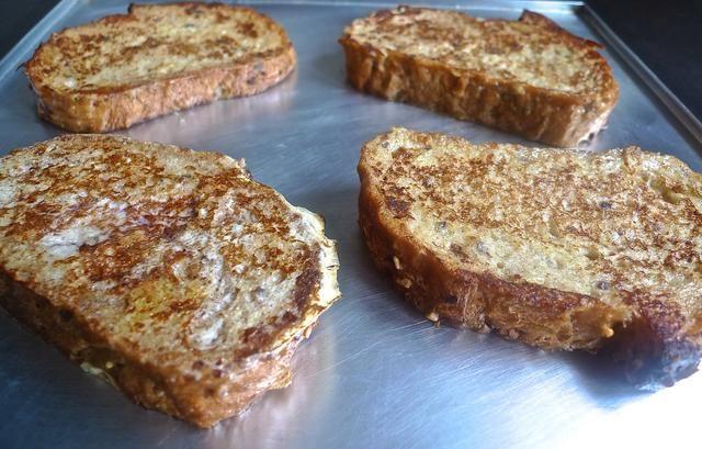 Transfiera las rebanadas marrones dorados de pan francés en una bandeja para hornear.