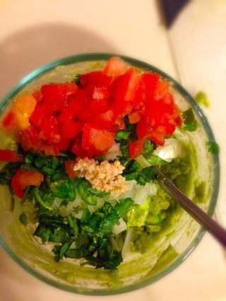 Añadir todas las verduras picadas al puré de aguacate. También agregue un poco de ajo picado