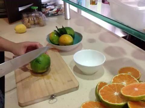 Quite las hojas de las naranjas y cortarlas por la mitad.