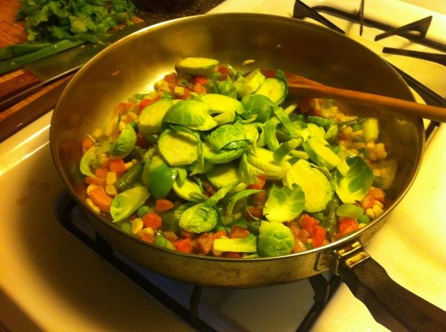 añadir el jamón, el ajo y las cebolletas juntos. sentar las coles de Bruselas en la parte superior. añadir pimienta molida fresca y albahaca seca al gusto.