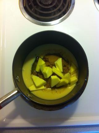 Coloque la mitad de la leche condensada, azúcar, jarabe de glucosa, jarabe de oro y la mantequilla en un cazo basado pesado a fuego lento.