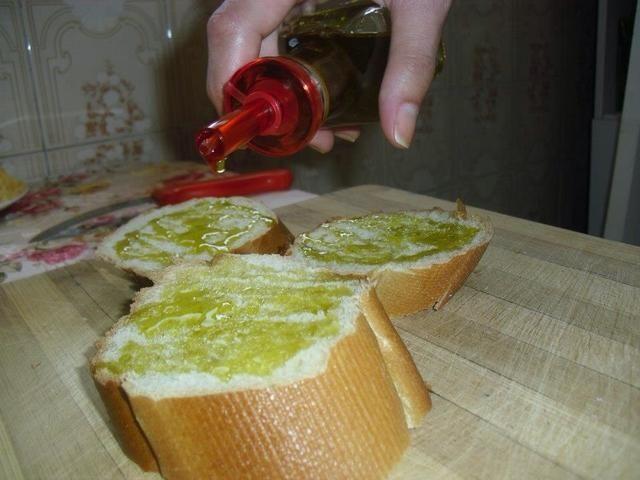Extender una capa de aceite de oliva versión extra para cada rebanada del pan.