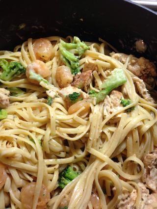 Agregue el pollo y camarón rallado con brócoli al vapor a la pasta y mezclar con la salsa Alfredo gradualmente