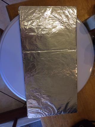 (Opcional) Recomendaría coger un mantel pastel para decorar tu pastel en. Hice éste con cartón y papel de aluminio