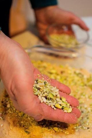Vierta la mezcla en un molde cuadrado ligeramente con mantequilla. Presione hacia abajo bien y aplanarlo. Espolvorear la parte superior con los pistachos y almendras de tierra. Pulse en bien.