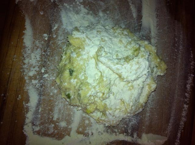 Gire la bola de masa pegajosa en una tabla bien enharinada y espolvorear con más harina.