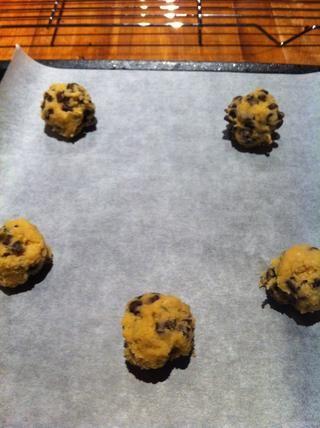 Cuchara bolas redondas de masa de galletas en papel de hornear