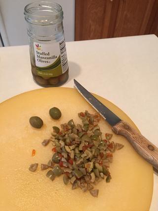 Mientras que las cebollas son cocinar, cortar las aceitunas.