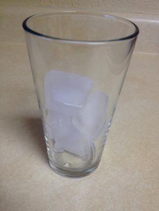 Coge un vaso alto y agregue los cubitos de hielo.