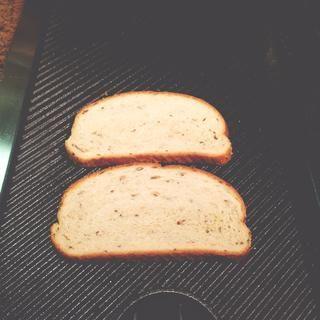 poner el pan con la cara de aceite de oliva sobre la parrilla. traer fuego a bajo.
