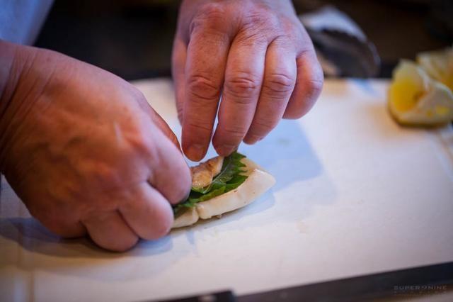 Calamares rodar hojas de shiso y lugar del lado de la costura hacia abajo en un plato para servir.
