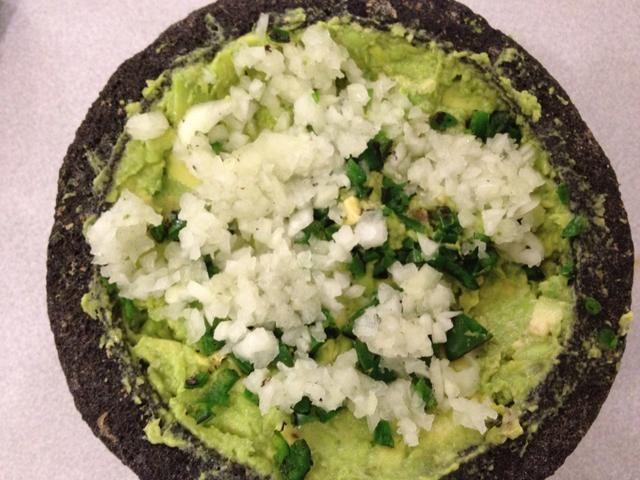 Añadir más cubitos de cebolla, jalapeño y cilantro al molcajete. Utilice la piedra o un tenedor para mezclar en la pasta de aguacate.