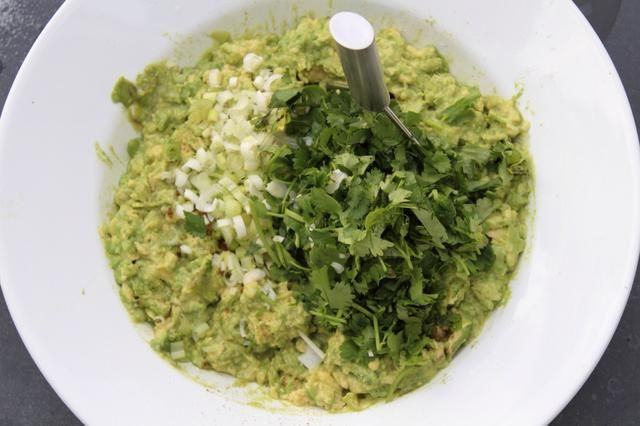 Utilice el machacador de nuevo para incorporar la cebolla y el cilantro en los aguacates.