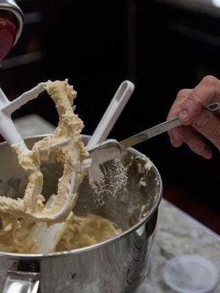 A continuación, agregue en el polvo de hornear. Mantenga raspando los lados del tazón.