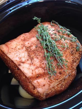 Coloque la carne de cerdo en la parte superior de la cebolla y poner tomillo fresco en la parte superior