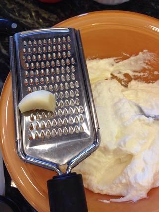 Rallar un diente de ajo sobre el yogur.