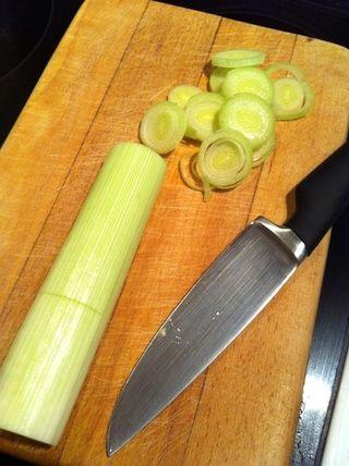 Cortar el puerro longitudinalmente por la mitad y cortar en tiras finas.