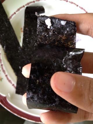 Enrolle el nori alrededor de las bolas de arroz y utilizar un lil bit de arroz para pegar el final. Ponlo a un lado