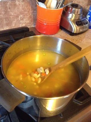 Añadir el caldo de pollo y frijoles a la olla.