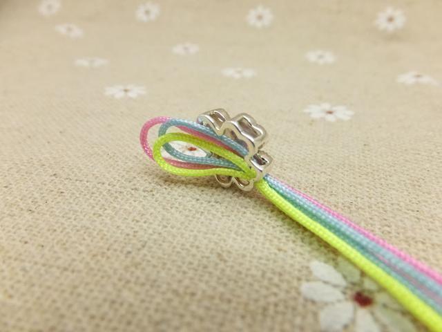 Tire de las otras dos cuerdas a través del agujero de la perla. A continuación, tire los tres cables a través del bucle. (Como se muestra en la imagen)