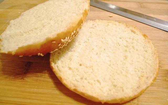 Cortar el pan de hamburguesa suave longitudinalmente a través del moño.