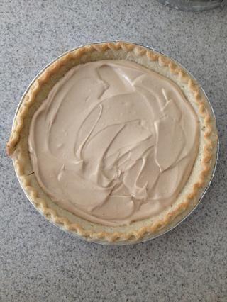 Vierta la mezcla de mantequilla de maní en la corteza de pastel ya cocido. Alisarla con una espátula o cuchara.