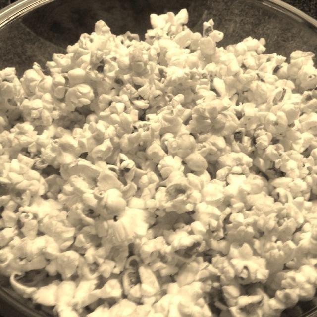 Aire pop 8 tazas de palomitas de maíz orgánico de acuerdo con las instrucciones de palomitas de maíz y popper aire. Siéntese a un lado en un bol.