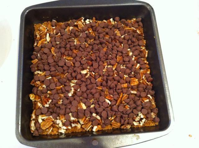 Espolvorear los trozos de chocolate de manera uniforme sobre las pacanas.