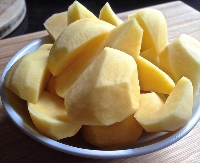 Cortar las patatas en trozos y sancochar las papas.