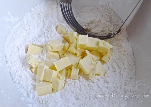 El uso de un cortapastas, cortar la mantequilla fría en la harina. También puede utilizar un procesador de alimentos para hacer esto.