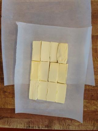 Cortar la mantequilla en tiras (corté tres piezas de cada palo, a lo largo) y el lugar en el papel de pergamino.
